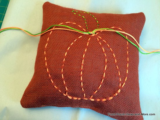 A cute little burlap pillow decorated with a pumpkin motif - just ribbon weaved in the burlap