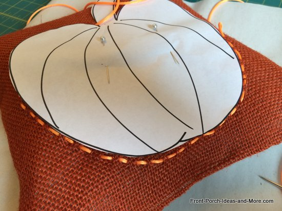 continue weaving the ribbon into a pumpkin shape onto the burlap