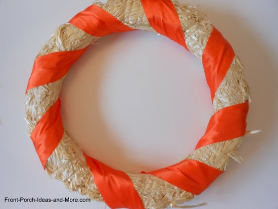 orange ribbon wrapped around the straw wreath