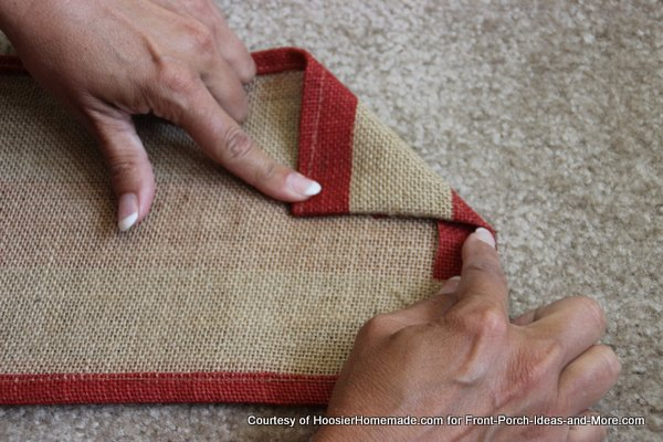 Liz folding the red burlap to make the point - first side
