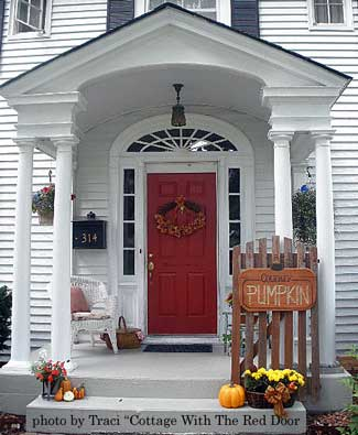 autumn decorated porch with picket fence and pumpkins