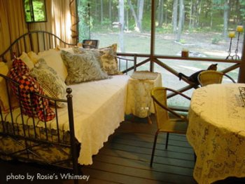 A comfortable sleeping porch with lots of pretty pillows
