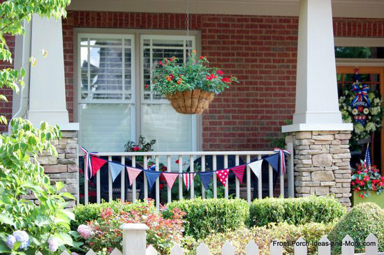 4th of July homemade pennant on front porch railing