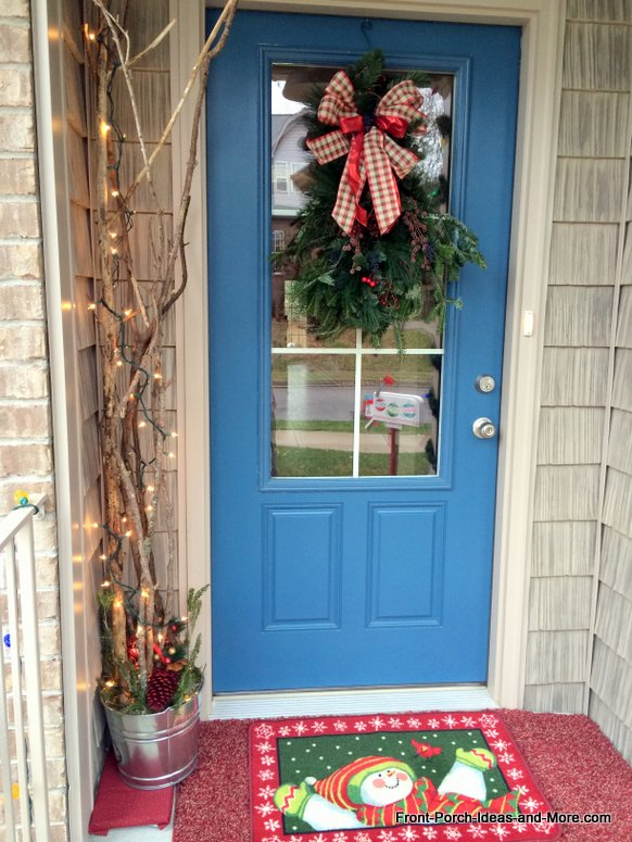 Plain branches decorated with sparkly lights inside a galvanized bucket - vintage Christmas at Front Porch Ideas and More