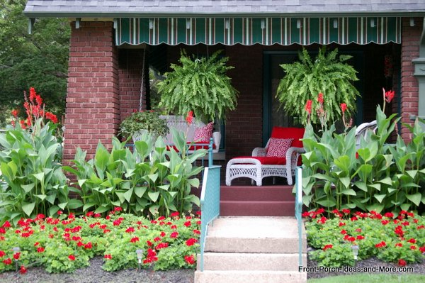 The porch landscaping incorporates red beautifully and the red cushions on the wicker chairs really pulls it all together