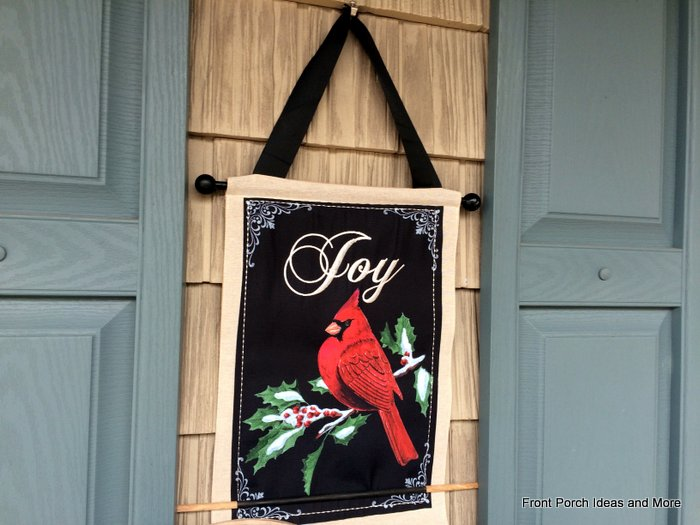 Joy winter wallhanging hangs between the shutters on our front porch
