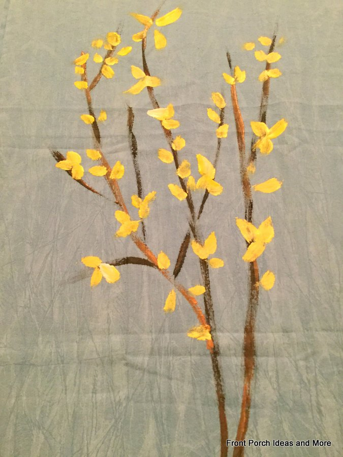 forsythia branches painted onto fabric with acrylic paints with most of the yellow blossoms added
