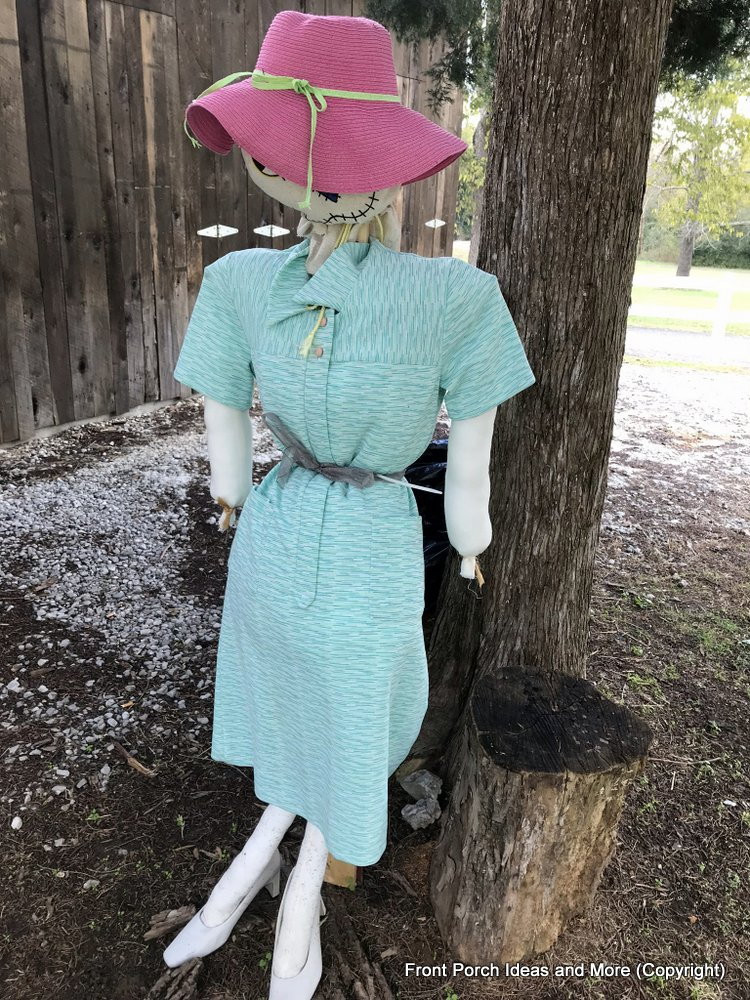 a lady scarecrow dressed in blue