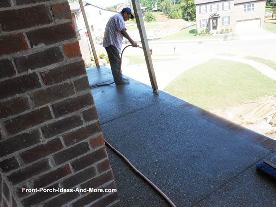 worker spraying concrete to expose aggregate concrete porch floor
