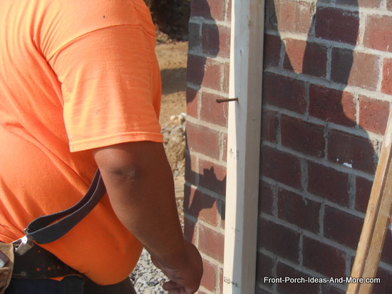 attaching 2x4s to brick porch wall for to begin framing