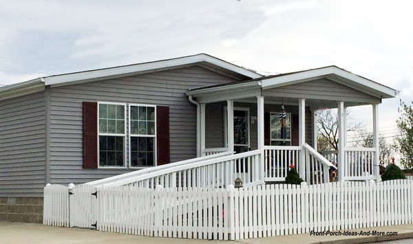 mobile home with wheel chair ramp and picket fence with front porch