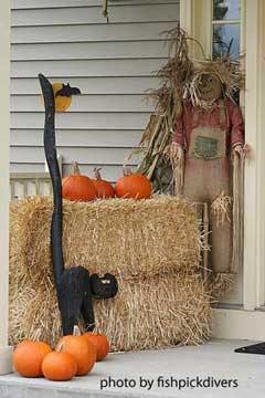 black cat and straw bale on porch