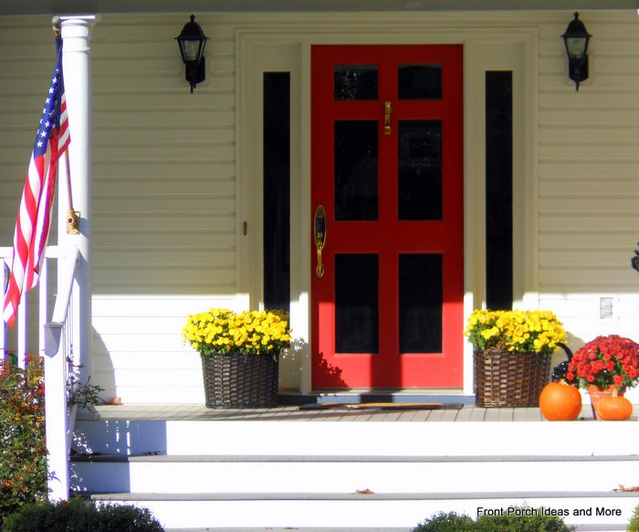 delightful fall front porch with red door and  mums