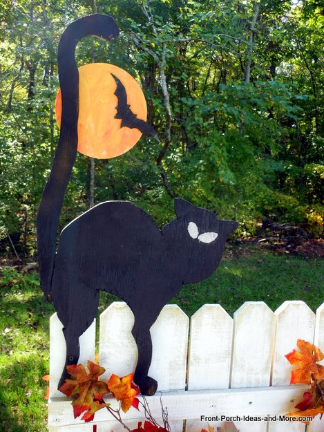 black cat, moon, and bat on fence