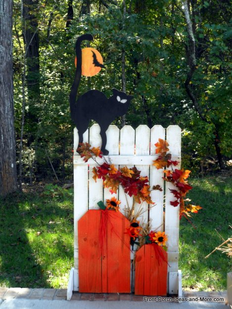 black cat and bat on fence