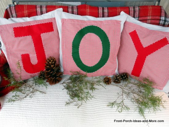 Three Christmas pillows that spell J-O-Y