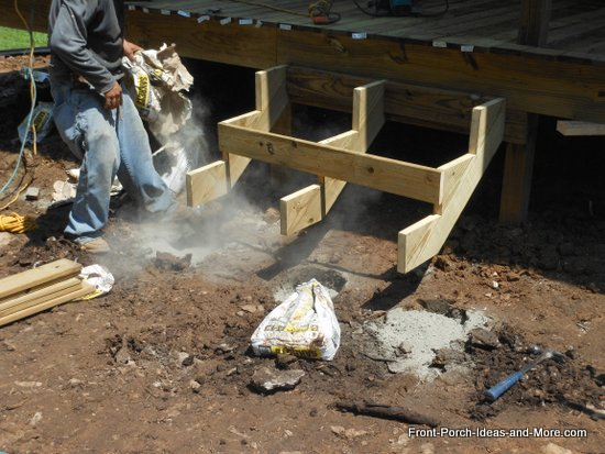 dry concrete is poured into holes for supporting posts