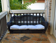 dark roast colored porch swing on stone porch floor