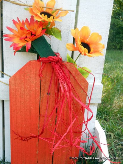 decorated wooden pumpkin on picket fence