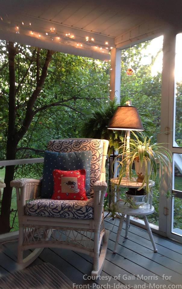 Comfortable rocking chair and side table with lamp on screen porch