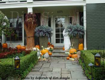 pumpkins and scarecrow as outdoor halloween decorations