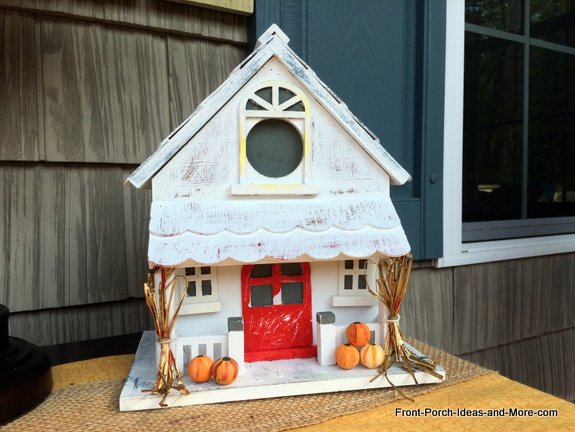 A decorative white-washed birdhouse with an autumn theme