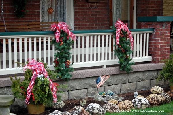 evergreen swags with Christmas bows on porch railings