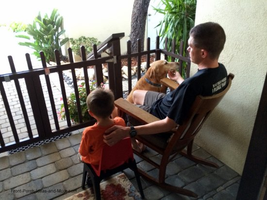 Father and son on porch with their dog