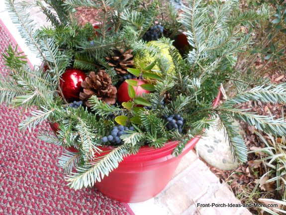 ornaments, pine cones,and osage oranges in bucket