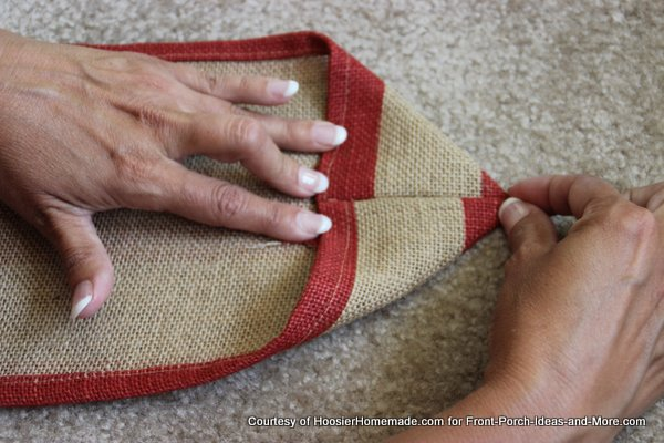 Liz folding the red burlap to make the point - second side