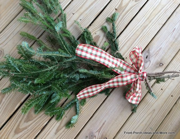 fresh greenery swag tied with ribbon for Christmas decoration - hanging on front door
