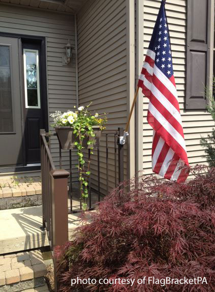 flag bracket attached to aluminum railing on front porch