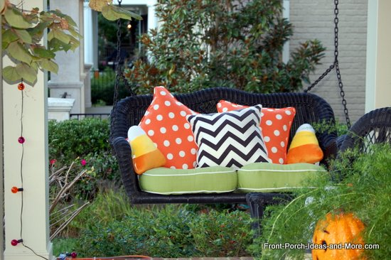 Very cute candy corn pillows on this porch swing