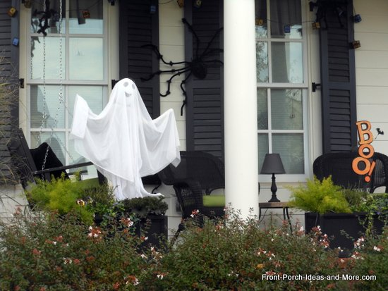 a friendly ghost greets trick-or-treats and a couple very furry spiders hang on the shutters