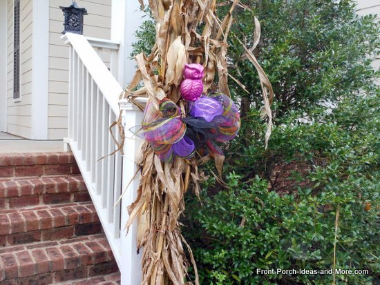 Cornstalks tied to porch step rails and decorate with colorful purple ribbons and cute owls