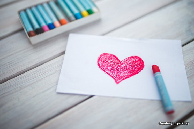 red heart drawn on paper with crayon