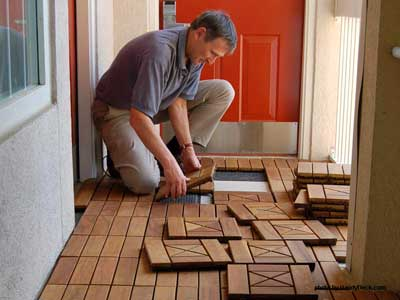 Man installing interlocking deck tiles