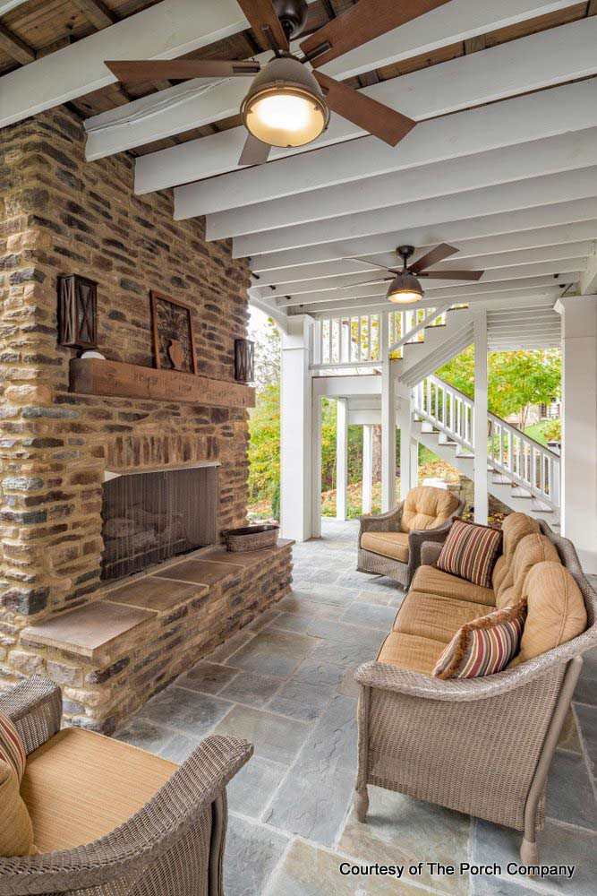 Screened porch with beautiful fireplace mantel by The Porch Company