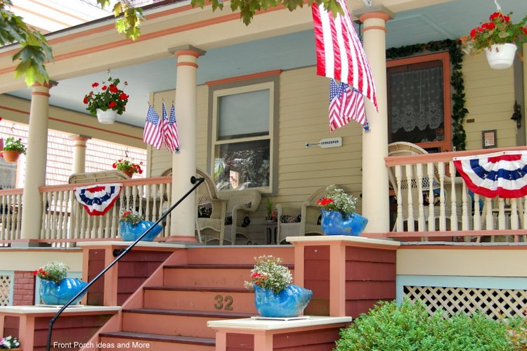 A patriotically decorated porch with a blue porch ceiling