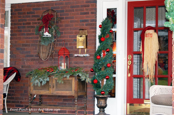 porch decorated with christmas trees, wicker furniture with plaid blanket, and santa wreath