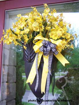 black basket at front door with yellow flowers, yellow ribbons and bkacn and white ribbons - very pretty