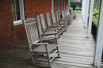 untreated porch rocking chairs aligned on long front porch