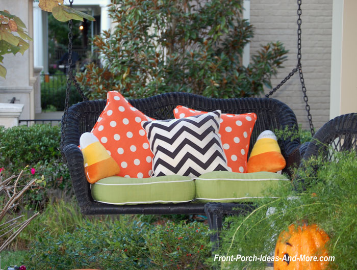 black wicker porch swing with colorful Halloween pillows