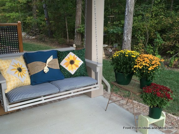 Our front porch swing with gray and white checked cushions and sunflower pillows.
