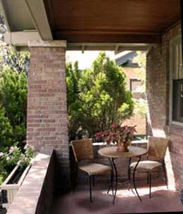 Privacy porch with high shrubs makes bistro set cozy secluded from neighbors