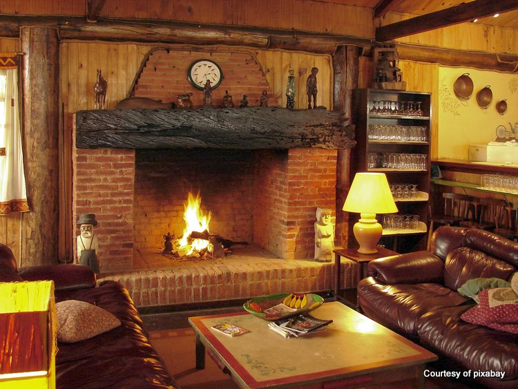 Brick fireplace with large mantel shelf and roaring fire in family room