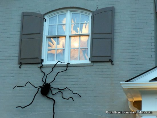 scary halloween decorations - giant person peeking out of window above and huge fuzzy spider