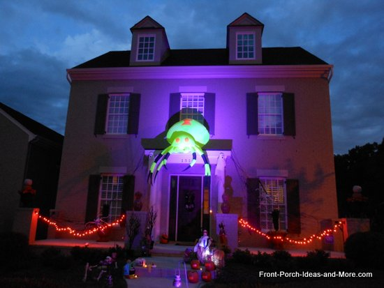 scary halloween decorations - big green bug atop this house