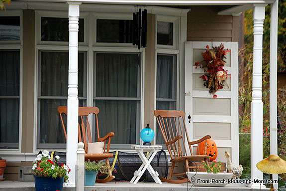 two rocking chairs and an old door decorated for autumn on front porch