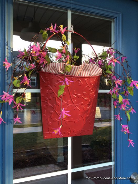 red metal basket filled with flowers on our front door for Valentine month